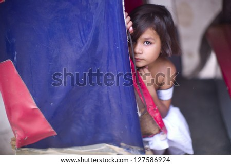 LAHORE, PAKISTAN- AUG 2: Unidentified child in brick kiln was shy when the relief team delivers food on August 2 2012 in Lahore, Pakistan. Poverty is a serious problem in Pakistan. - stock photo