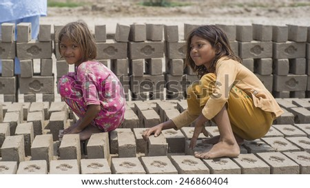 LAHORE, PAKISTAN- AUG 1 2012: Unidentified children work at a brick kiln on August 1 2012 in Lahore, Pakistan. Children are exploited in the brick kiln and they suffer from poor education.  - stock photo