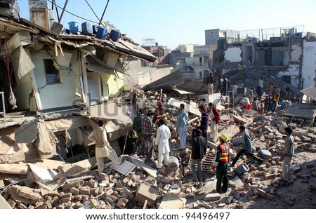 LAHORE, PAKISTAN - FEB 06: Rescue workers look for survivors in the debris at the site of building collapse incident on February 06, 2012 in Lahore.