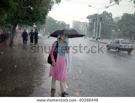 LAHORE, PAKISTAN-SEPT 02: A girl holds umbrella over her head passes through Mall  road during heavy downpour in Lahore on Thursday, September 02, 2010.  (Babar Shah/PPI Images).