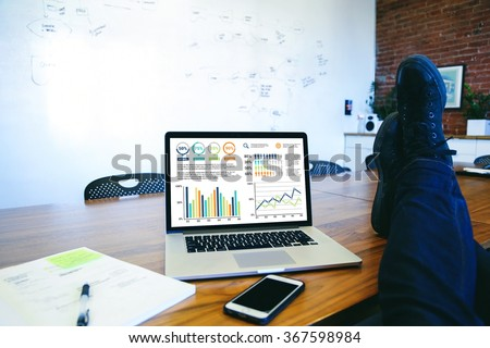 Laid back man putting feet up on table with a laptop showing business graphic charts. - stock photo