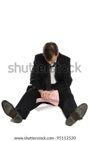 Laid off businessman sits depressed on the floor, isolated on white background - stock photo