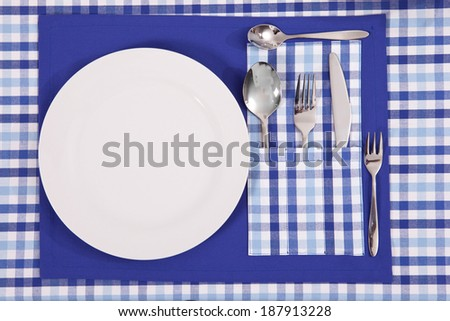 laid table/ fork and spoon laid on blue cloth in the kitchen