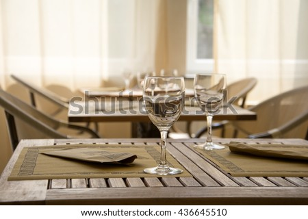 Laid table in a ethnic restaurant. Wooden table with two wine glasses.