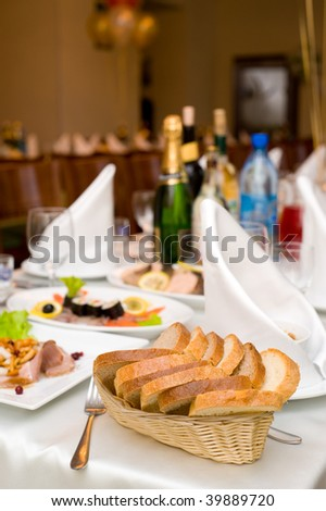 laid table with tableware and dishes for banquet, focus on basket of bread