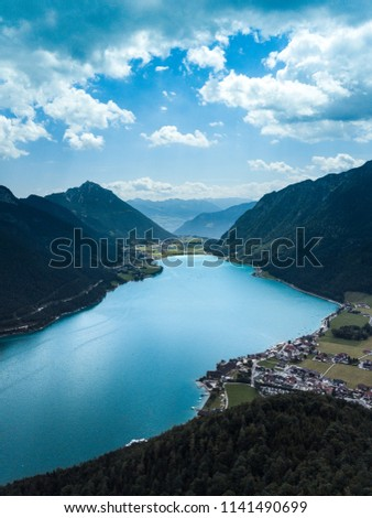 Lake Achen in Austria with mountains in the background and plenty of clouds in the sky. Summer day at the lake.