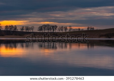 Lake after sunset landscape. Close up of opposite shore of lake with trees and sky reflected in water. Beautiful landscape.
