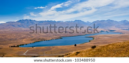 Lake Alexandrina in dry grassland in Central Canterbury with ranges of suthern alps, South Island, New Zealand - stock photo