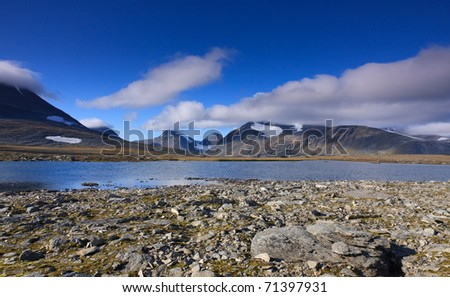 Lake and blue sky  high in the Arctic mountains in Sweden. - stock photo