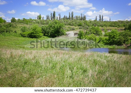 Lake and green hills under blue sky