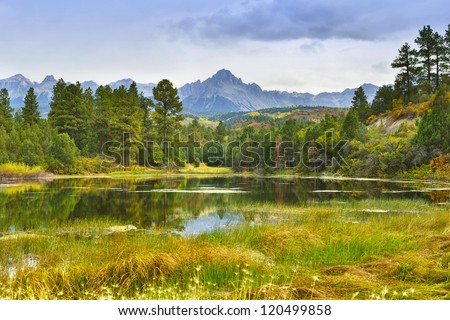 lake and mountain with golden and green trees in colorado during fall - stock photo