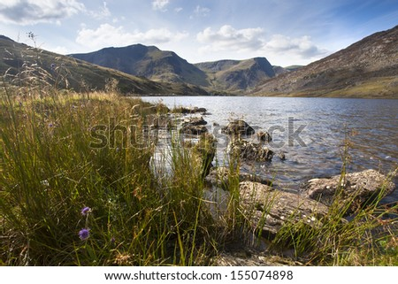 lake and mountains in summer sunlight in snowdonia, north wales - stock photo