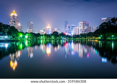 Lake and skyscrapers at night, at Lumphini Park, in Bangkok, Thailand.