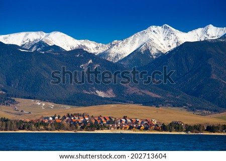 Lake and village at Tatras mountains and white peaks above - stock photo
