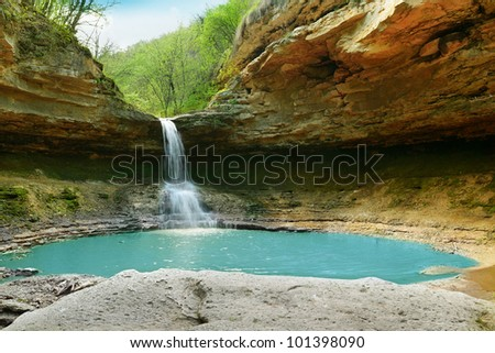 lake and waterfall in the forest - stock photo