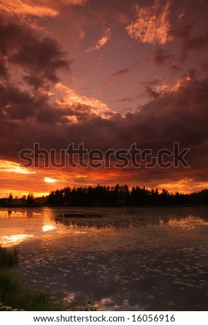Lake at sunset with reflection in Finland - stock photo