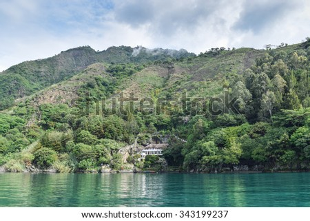 Lake Atitlan, Guatemala â?? June 6, 2015: Luxury homes line the banks of Lake Atitlan in the Guatemalan Highlands, where local people still live traditional lifestyles and worship ancient Mayan gods.