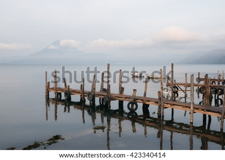 Lake Atitlan with piers and volcano, early morning. Guatemala. - stock photo