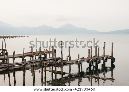 Lake Atitlan with piers and volcanoes in the distance. Early morning. - stock photo