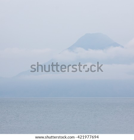 Lake Atitlan with volcano and clouds, early morning. Guatemala. - stock photo