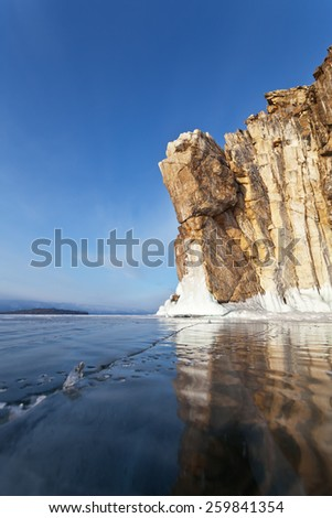 Lake Baikal. Beautiful cliffs reflected in the smooth ice - stock photo