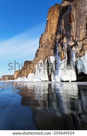 Lake Baikal. Coastal cliffs reflected in the smooth ice. Winter landscape - stock photo