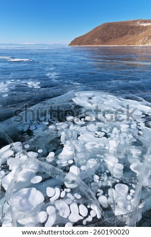 Lake Baikal in winter. Beautiful white bubbles in the interior of transparent ice - stock photo
