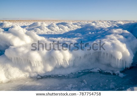 Lake Baikal in winter. Ice-covered cliffs with beautiful huge icicles