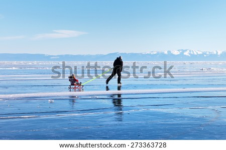 LAKE BAIKAL, IRKUTSK REGION, RUSSIA - March 21, 2015: Father with his son are traveling on the frozen lake ice skating and sledding, Baikal Lake, Irkutsk region, Russia  - stock photo