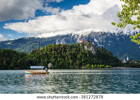 Lake Bled, Slovenia - 24 May 2015: A pletna boat serving visitors across lake bled with Bled Castle as background