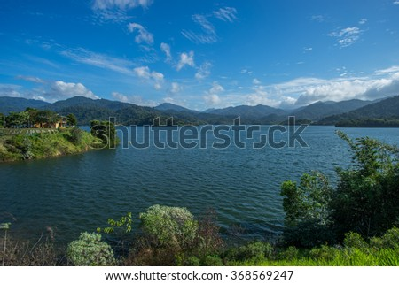 Lake dam with blue sky and forest on background.