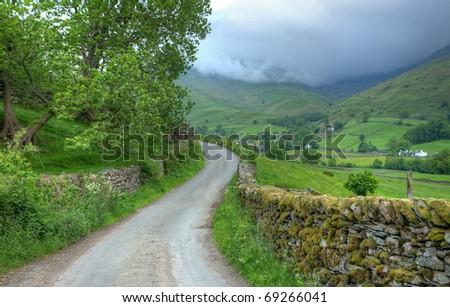 Lake District landscape with lane leading to Low Mill Bridge, Grasmere, Cumbria, England. - stock photo