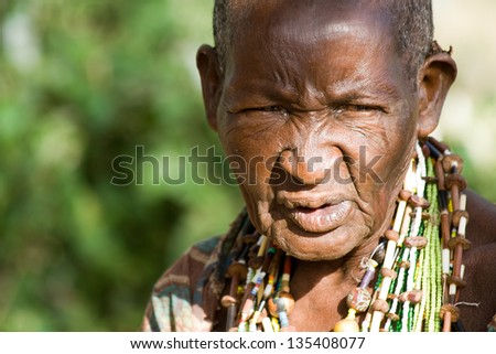 LAKE EYASI, TANZANIA - FEBRUARY 18: An unidentified old Hadzabe woman looks seriously in the bush on February 18, 2013 in Tanzania. Hadzabe tribe threatened by extinction.