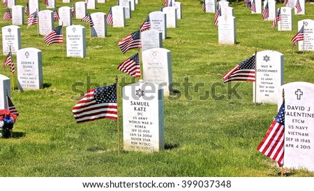 Lake Forest, IL, USA - May 23, 2015: A Memorial Day (Decoration Day) view at Fort Sheridan Cemetery of tombstones decorated with American flags, engraved with Christian Cross, Jewish Star of David.   - stock photo