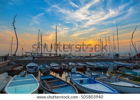 LAKE GARDA, ITALY - SEPTEMBER 2016 : Sailboats fishing boats at Porto di Bardolino harbor on The Garda Lake during sunset in Italy on September 24, 2016. It is largest lake in Italy