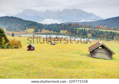 Lake Geroldsee in colorful autumn season, a beautiful alpine lake between Garmisch-Partenkirchen and Mittenwald with foggy Karwendel mountains in the background, Gerold, Bavaria, Germany - stock photo