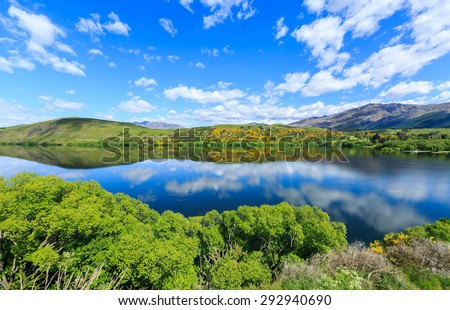 Lake Hayes located in Otago Region, Queenstown, South Island, New Zealand. This shot taking in summer showing its reflection of the Lake and vibrant colour. - stock photo