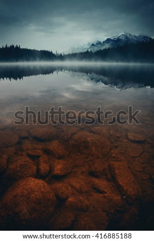 Lake Herbert in a foggy morning with glaciers mountain and reflection in Banff National Park, Canada - stock photo