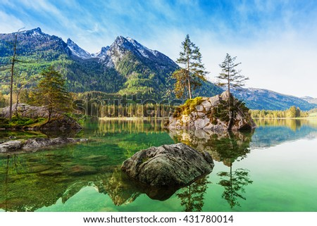 Lake Hintersee in beautiful scene of trees on a rock island in idyllic scenery at charming  with blue sky and clouds in spring, Nationalpark Berchtesgadener Land, Upper Bavaria, Germany
