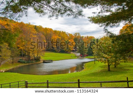 Lake house surrounded by Fall foliage. Scenic autumn view of North Carolina home framed with tree branches and country fence - stock photo