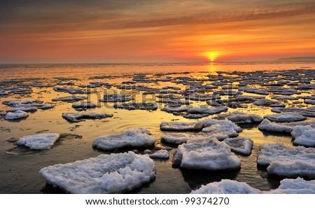 Lake Huron Sunrise - floating ice in this Lake Huron Winter scenic , Port Hope, Michigan USA - stock photo