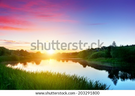 Lake in forest at sunset. Peaceful and calm mood. Romantic sky with red clouds - stock photo