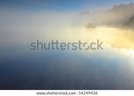 Lake in morning mist - stock photo