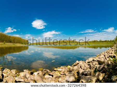 lake in mountain surrounded by oak wood by autumn - stock photo