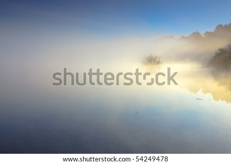 Lake in the early morning mist - stock photo