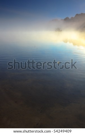 Lake in the mist - stock photo