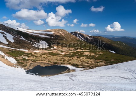 Lake in the mountains. Spring landscape with blue sky and cumulus clouds. Sunny day. The last snow on the slopes. Carpathians, Ukraine, Europe - stock photo