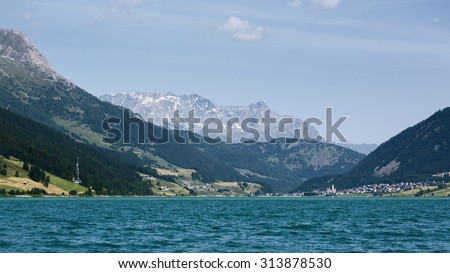 Lake Lago di Resia or Reschensee by summer with the surrounding Alpine mountaintops. - stock photo