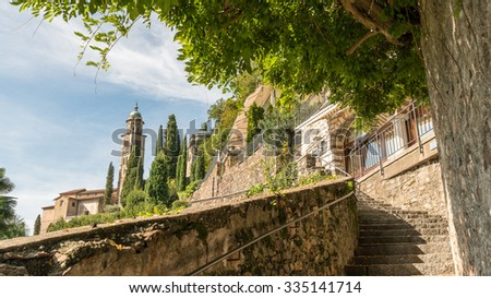 Lake Lugano, Switzerland, Beautiful Panorama Ancient Stone Stairway trail path to Chiesa Santa Maria del Sasso Church under Clear Blue Sky in Summer, Morcote - stock photo