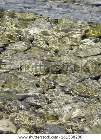 Lake Michigan phenomenon of dazzling fluctuation: Shallow water shimmering over glacial rocks in afternoon sunlight on shoreline of Door County, Wisconsin, USA - stock photo